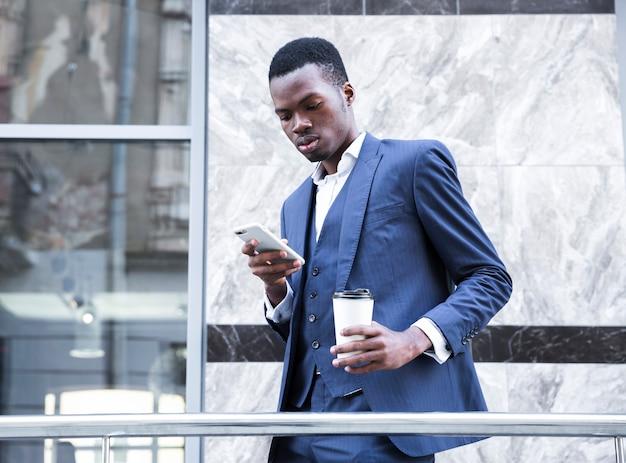 Un hombre de negocios joven africano que sostiene la taza de café disponible usando el teléfono móvil