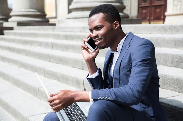 Hombre de negocios joven africano sonriente que habla en el teléfono móvil que se sienta en escalera con el ordenador portátil