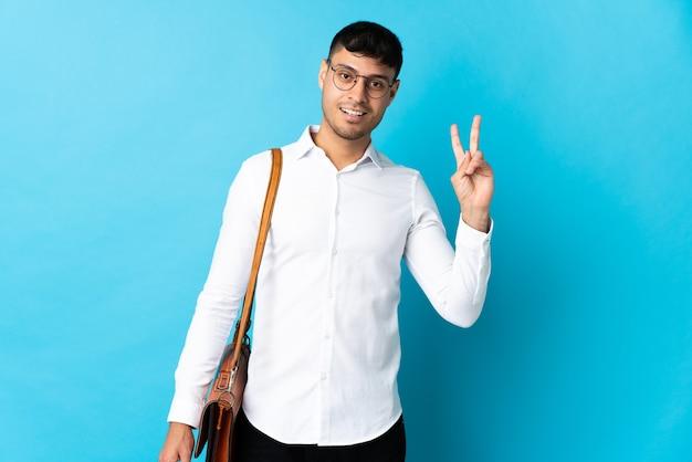 Hombre de negocios joven aislado en azul sonriendo y mostrando el signo de la victoria