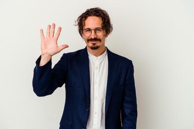 Hombre de negocios joven aislado en la pared blanca sonriendo alegre mostrando el número cinco con los dedos
