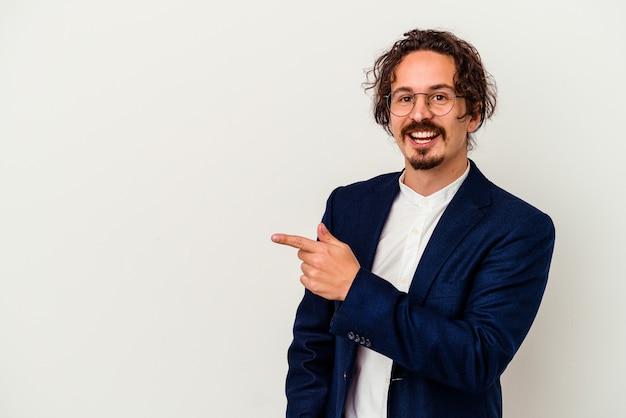 Hombre de negocios joven aislado en la pared blanca sonriendo y apuntando a un lado, mostrando algo en el espacio en blanco