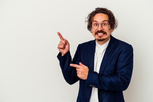 Hombre de negocios joven aislado en la pared blanca sorprendido apuntando con los dedos índices a un espacio de copia
