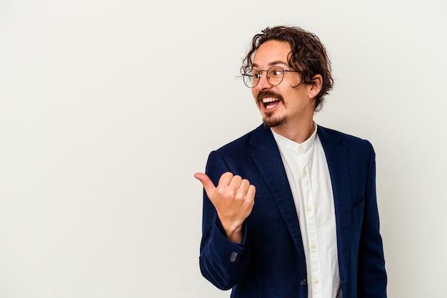 Hombre de negocios joven aislado en puntos de pared blanca con el dedo pulgar, riendo y despreocupado