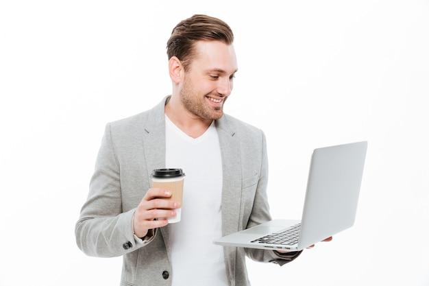 Hombre de negocios joven alegre que bebe el café usando la computadora portátil