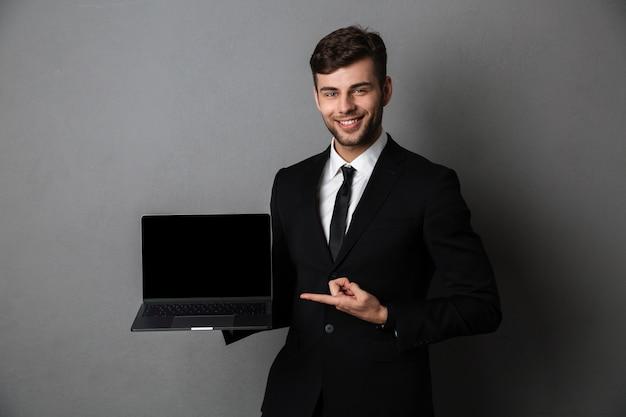 Hombre de negocios joven alegre que muestra la pantalla de la computadora portátil