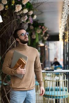 Hombre de negocios joven de alto ángulo con laptop y agenda