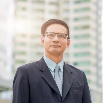 Hombre de negocios joven de asia delante del edificio moderno en el centro de la ciudad.