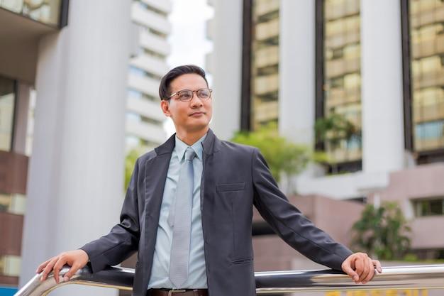 Hombre de negocios joven de asia frente al moderno edificio en el centro de la ciudad