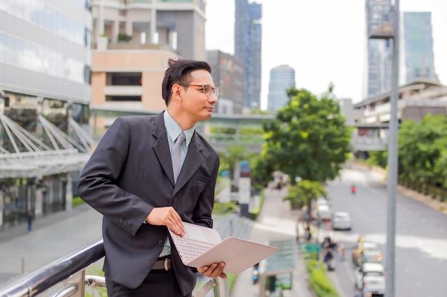 Hombre de negocios joven de asia en traje con su computadora portátil al aire libre, edificio moderno en el fondo