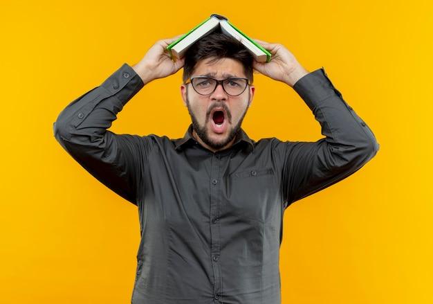 Hombre de negocios joven asustado con gafas cubrió la cabeza con el libro aislado en amarillo