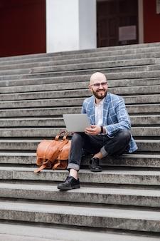 Hombre de negocios joven barbudo se sienta en los pasos usando la computadora portátil y mira en su pantalla.