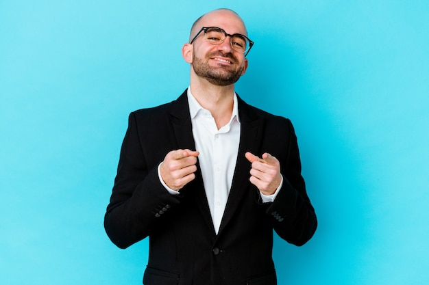 Hombre de negocios joven calvo caucásico aislado sobre fondo azul sonrisas alegres apuntando al frente.