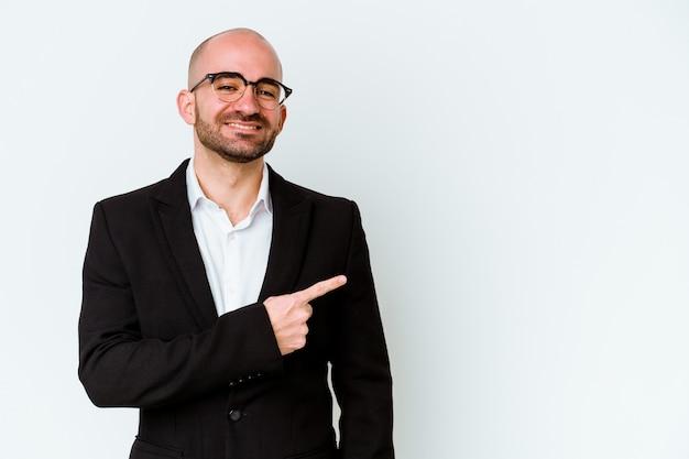 Hombre de negocios joven calvo caucásico aislado sobre fondo blanco sonriendo y apuntando a un lado, mostrando algo en el espacio en blanco.