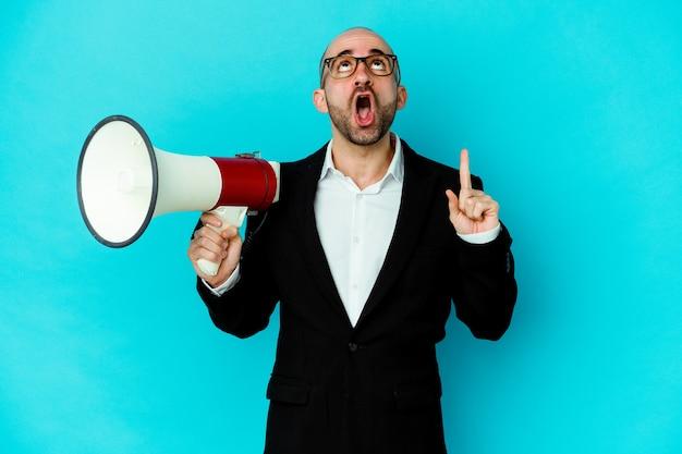 Hombre de negocios joven calvo sosteniendo un megáfono aislado apuntando al revés con la boca abierta.