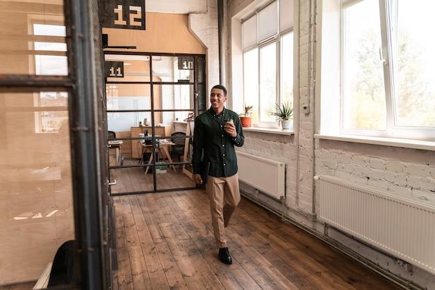 Hombre de negocios joven caminando en los pasillos de la oficina. concepto sobre negocios y personas