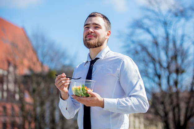 Hombre de negocios joven en camisa y lazo con la caja de almuerzo de la ensalada