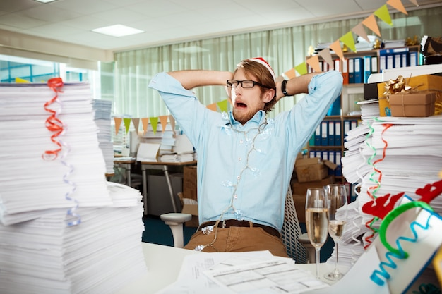 Hombre de negocios joven cansado que se sienta en el lugar de trabajo entre los papeles el día de navidad.