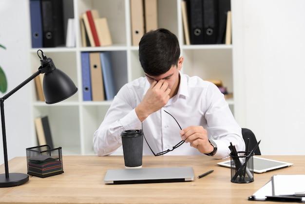 Hombre de negocios joven cansado que sostiene las lentes disponibles con la taza y el ordenador portátil de café para llevar en el escritorio