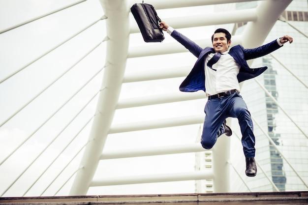 El hombre de negocios joven con una cartera que se ejecuta en una calle de la ciudad se apresura para ir a trabajar.