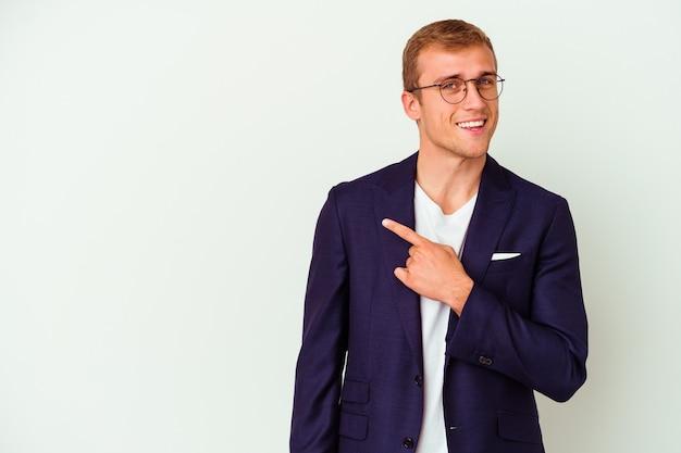 Hombre de negocios joven caucásico aislado sobre fondo blanco sonriendo y apuntando a un lado, mostrando algo en el espacio en blanco.