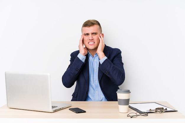 Hombre de negocios joven con una computadora portátil que cubre los oídos con las manos.
