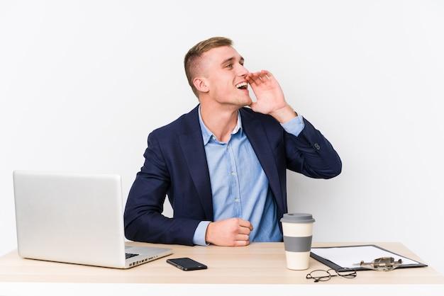 Hombre de negocios joven con una computadora portátil que grita y que sostiene la palma cerca de boca abierta.