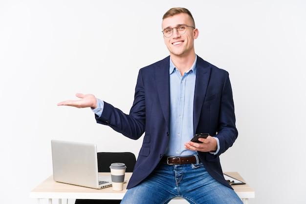 Hombre de negocios joven con una computadora portátil que muestra un espacio de la copia en una palma y que lleva a cabo otra mano en la cintura.
