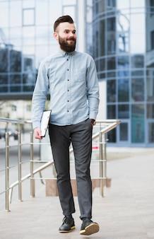 Hombre de negocios joven confiado que camina delante del edificio corporativo