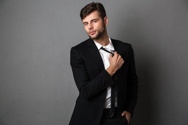 Hombre de negocios joven confidente hermoso en traje negro que endereza su corbata