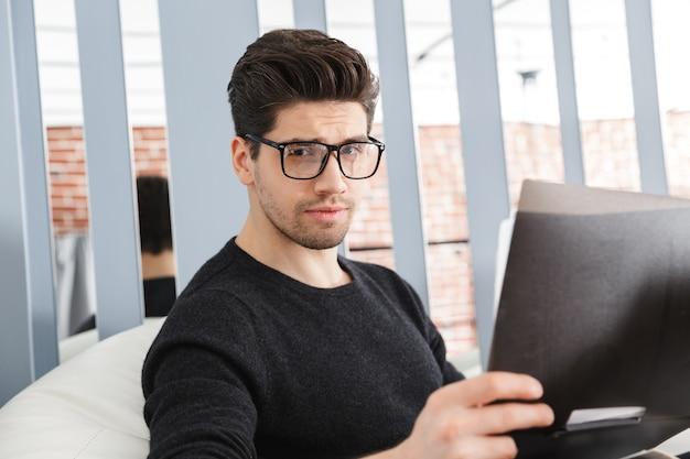 Hombre de negocios joven confidente que trabaja en la oficina mientras está sentado en un sofá, analizando documentos