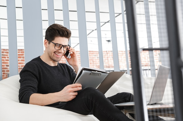 Hombre de negocios joven confidente que trabaja en la oficina mientras está sentado en un sofá, hablando por teléfono móvil