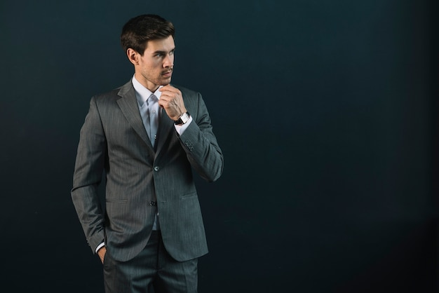 Hombre de negocios joven contemplado contra fondo negro