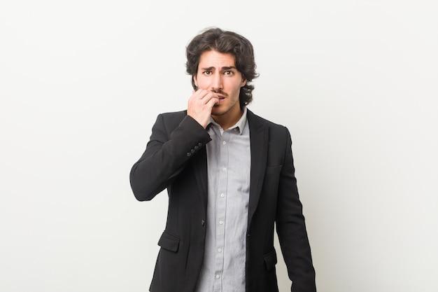 Hombre de negocios joven contra un fondo blanco morderse las uñas, nervioso y muy ansioso.