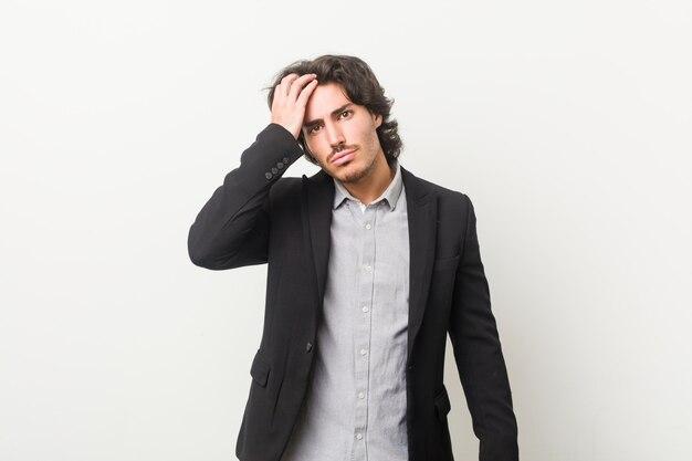Hombre de negocios joven contra una pared blanca cansado y con mucho sueño manteniendo la mano en la cabeza