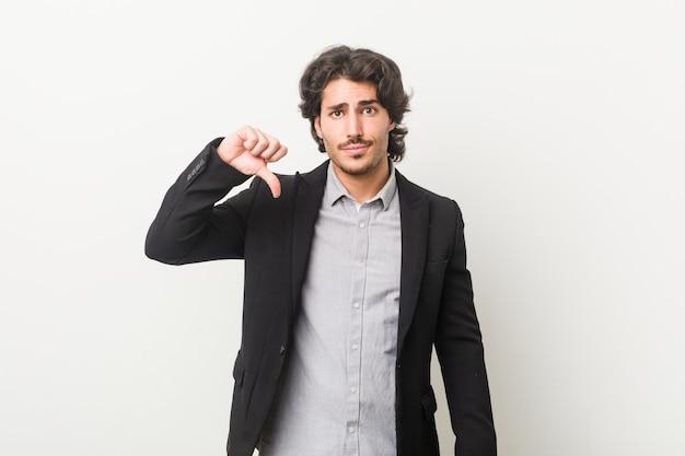Hombre de negocios joven contra una pared blanca que muestra un gesto de disgusto, pulgares abajo. concepto de desacuerdo