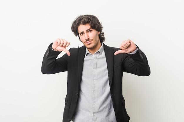 Hombre de negocios joven contra una pared blanca que muestra el pulgar hacia abajo y que expresa aversión.