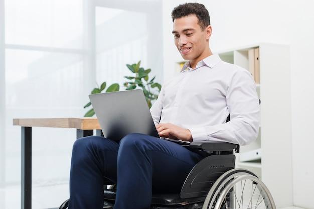 Hombre de negocios joven discapacitado feliz que se sienta en la silla de ruedas usando el ordenador portátil en la oficina