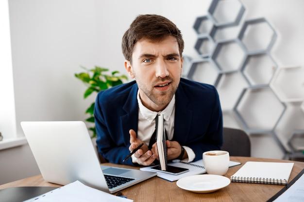 Hombre de negocios joven disgustado que se sienta en el lugar de trabajo, fondo de la oficina.