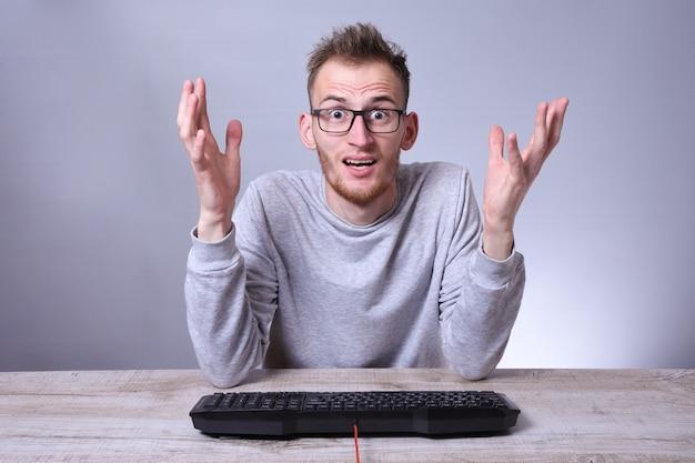 Hombre de negocios joven divertido del empollón que trabaja en la computadora
