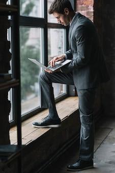 Hombre de negocios joven elegante que se coloca cerca de la ventana que mecanografía en el ordenador portátil