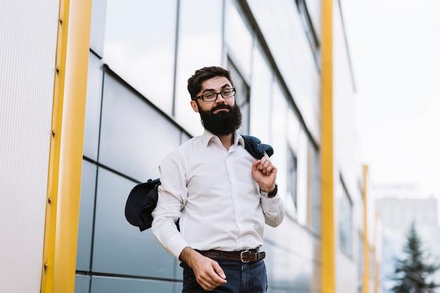 Hombre de negocios joven elegante que sostiene la capa sobre su hombro que se coloca delante del edificio