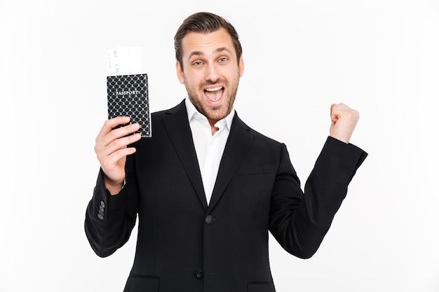 Hombre de negocios joven emocionado feliz que sostiene el pasaporte