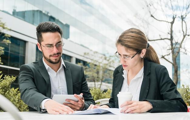 Hombre de negocios joven y empresaria que se sientan en el café al aire libre que mira el documento