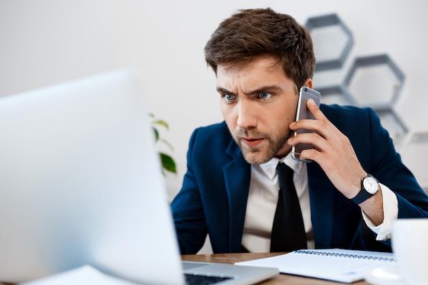 Hombre de negocios joven enfadado que habla en el teléfono, fondo de la oficina.