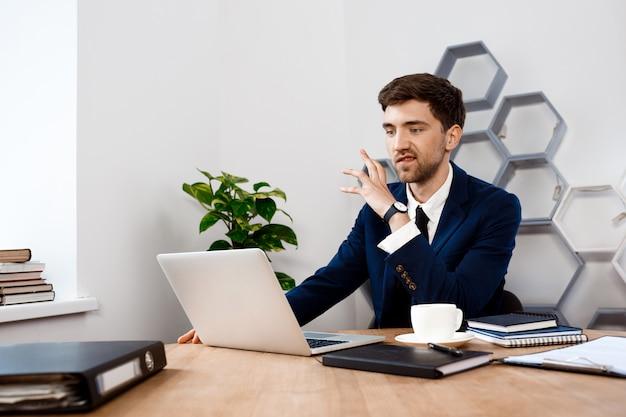 Hombre de negocios joven enfadado que se sienta en la computadora portátil, fondo de la oficina.