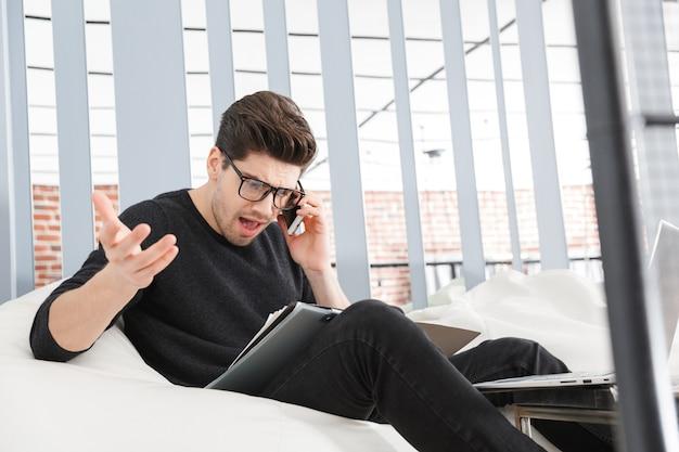 Hombre de negocios joven enojado que trabaja en la oficina mientras está sentado en un sofá, hablando por teléfono móvil
