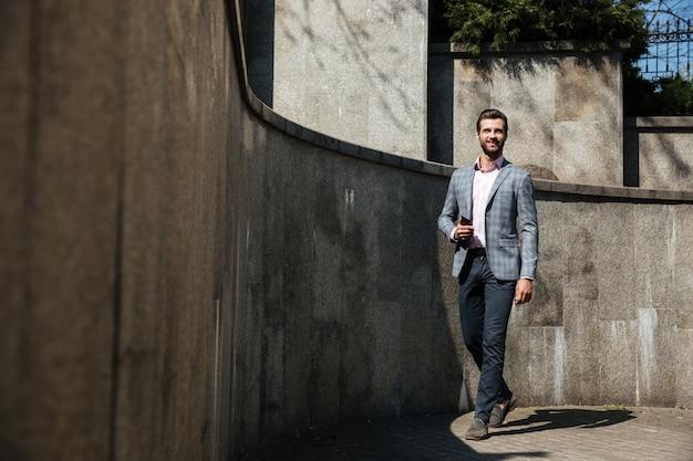 Hombre de negocios joven feliz que camina al aire libre que sostiene el teléfono