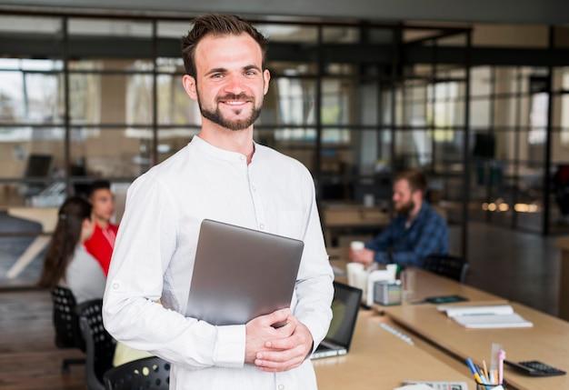 Hombre de negocios joven feliz que mira la cámara que sostiene el ordenador portátil en oficina