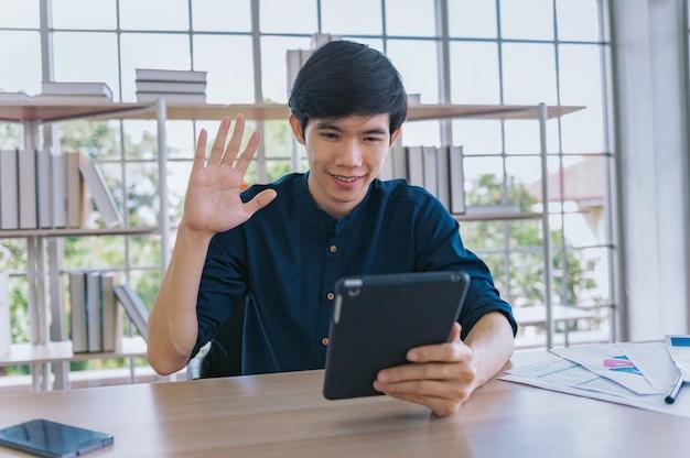 Hombre de negocios joven feliz sonriendo videollamada con un amigo en casa. concepto de trabajo quedarse en casa