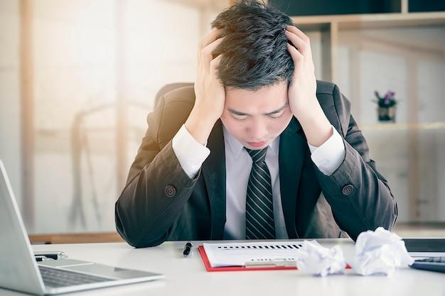 Hombre de negocios joven frustrado cansado que siente estresado, sosteniéndose principal y preocupado sobre busine